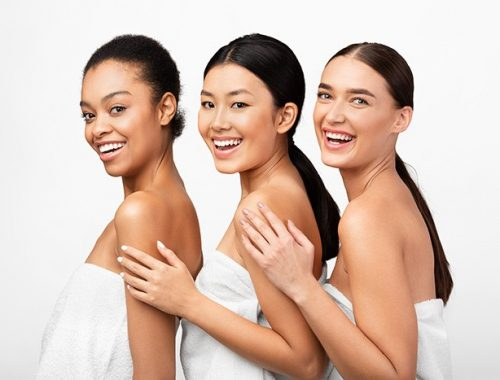 Beauty And Skincare. Three Mixed Model Girls In Bath Towels Posing Smiling To Camera Over White Studio Background